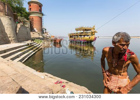 VARANASI, INDIA - MAR 13, 2018: Pilgrims on the banks of Holy Ganga river. Varanasi is one of the most important pilgrimage sites in India and is one of the 7 sacred cities of Hinduism.