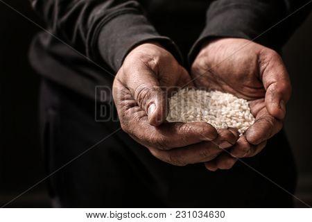 Poor man holding rice in hands on dark background