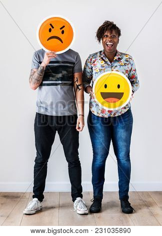 Interracial couple holding an expressive emoticon face facial expression frown and smile relationship issue concept