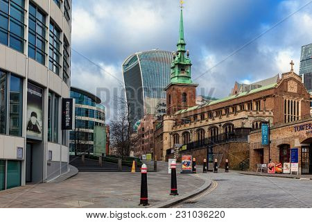 LONDON, UK - JANUARY 12, 2016: Urban view of modern buildings and All Hallows by the Tower - famous ancient Anglican church founded in 675. It is one of the oldest churched in London.