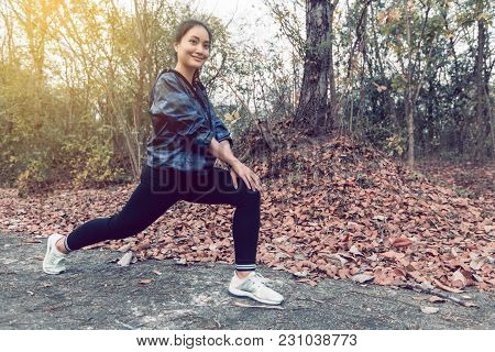 Athletic Woman Asia Warming Up And Young Female Athlete Exercising And Stretching In A Park Before R