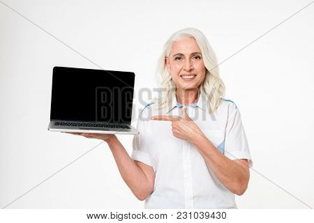 Image of adult woman with grey hair smiling and pointing finger on copyspace screen of laptop, isolated over white background