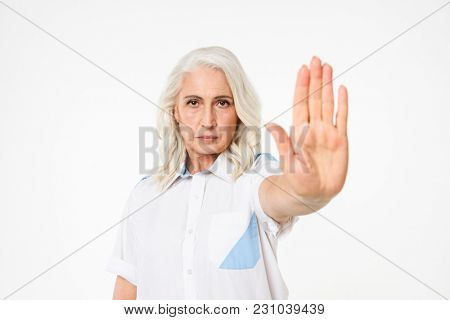 Picture of serious mature woman with grey hair looking strictly on camera expressing total rejection and gesturing to stop with hand isolated over white background