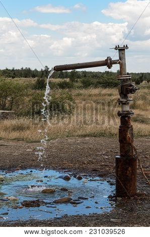 The Flow Of Water Flowing Through The Tap From Underground Water In The Middle Of The Steppe. The Fl