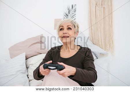 An Elderly Woman Is Playing A Video Game. Elderly Person And Modern Technology