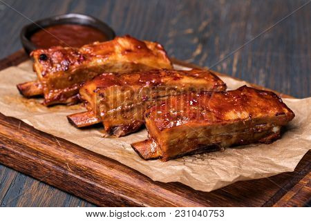 Grilled pork ribs in barbecue sauce on wooden plate