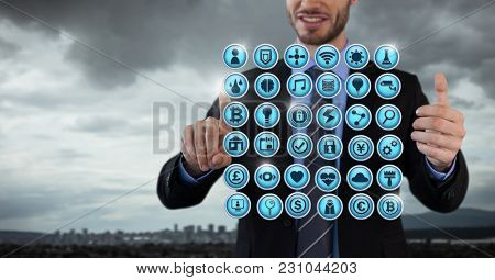 Digital composite of Various app icons rowed and Businessman with hands touching air in city office