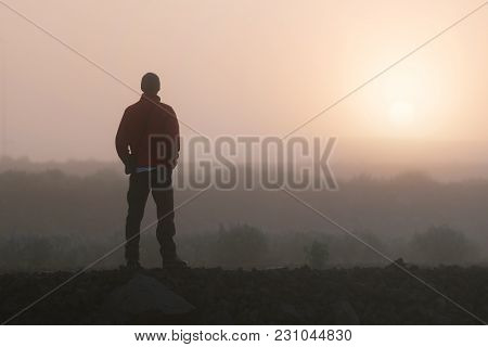Man thinks looking at the rising sun. Morning landscape with fog