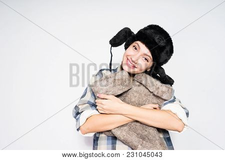 Happy Young Russian Girl In A Warm Fur Hat Holds Winter Boots In Her Hands