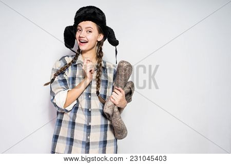 Funny Young Russian Girl Smiling, Wearing A Fur Hat On Her Head, Holding Warm Gray Felt Boots