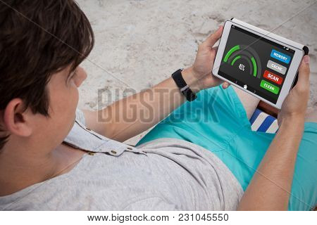 Mobile display with memory cleaner against man using digital tablet on the beach