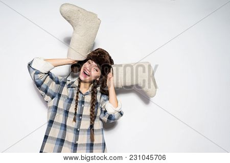 Laughing Young Russian Girl In Fur Hat Rejoices In Winter, Holds Gray Felt Boots In Hands