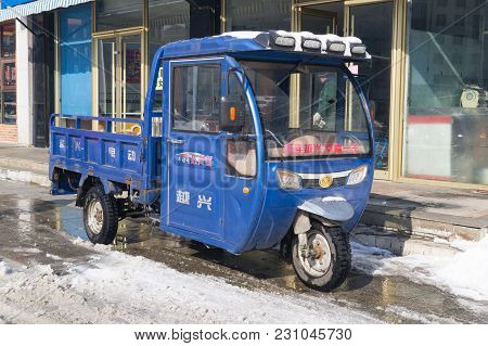 Hunchun, Jilin, China - March 8, 2018: Three-wheel Motor Scooter With A Cab Is Traditionally Used Fo