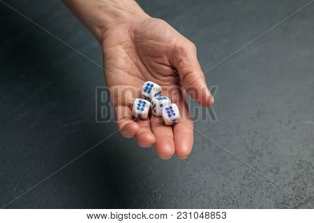 Dice. The Female Hand Holds Dice. Dark Background