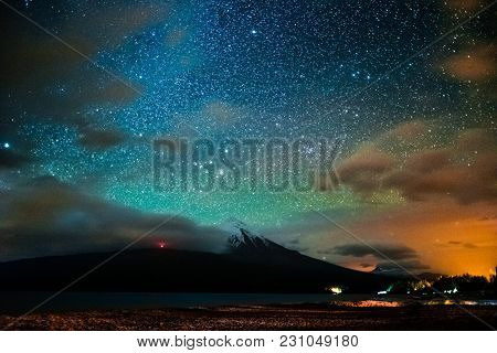 Starry sky and the volcano of Osorno with clouds highlighted by town, Chile. High level of noise