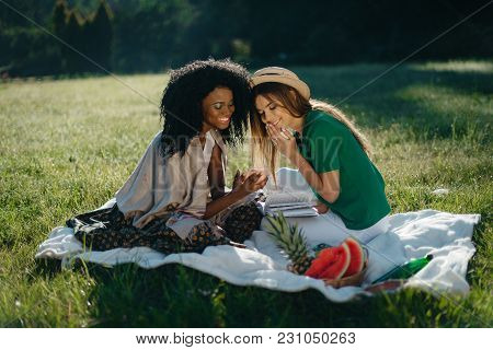 Two Multi-ethnic Girls Are Having Fun On The Picnic. The Charming Young African Girl Is Showing Sone