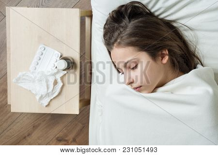 Cold Flu Season. Sick Girl Child In Bed, Near Bed Medication Napkin.