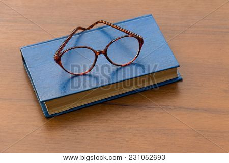 Closed Book And Eyeglasses On Wooden Background