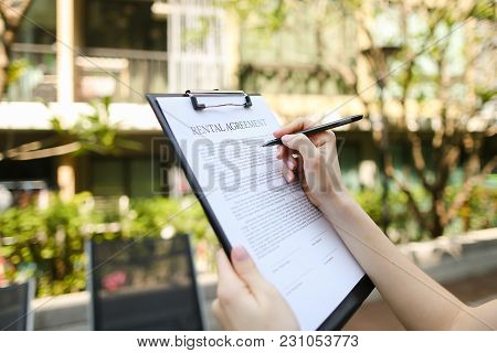 Close Up Portrait Of Woman Hands Signing Rental Agreement On Background Of Leasing Office Apartments
