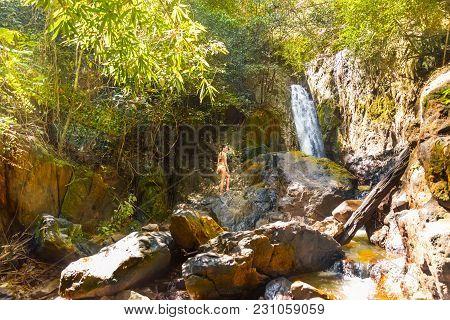 Young Woman In A Bikini Stands On Rock Waterfall