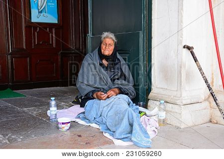 Lagos, Portugal - June 9, 2017 - Destitute Old Lady Sitting In The Santa Maria Church Doorway, Lagos