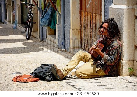 Lagos, Portugal - June 9, 2017 - Street Performer Sitting On The Pavement Playing A Guitar And Singi