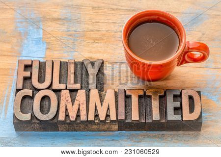 fully commited  - word abstract in vintage letterpress  wood type with a cup of coffee