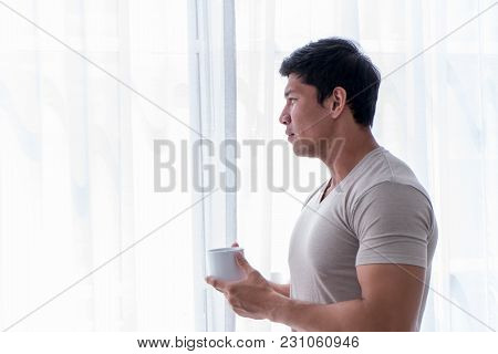 Asian Strong Man Is Drinking Tea Coffee By The Morning Windows