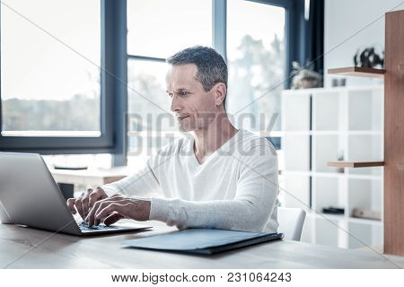 Concentration And Work. Confident Pleasant Handsome Employee Sitting In The Cabinet By The Table Smi