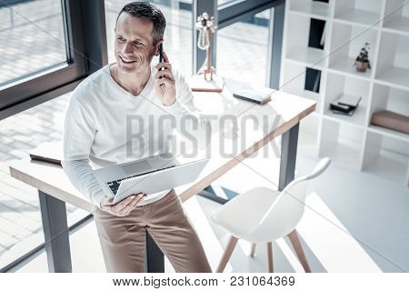 Im Listening. Perspective Skilled Confident Employee Leaning On The Table In His Cabinet Holding Lap
