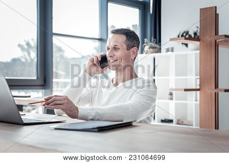 New Project. Occupied Satisfied Perspective Employee Sitting By The Table In The Cabinet Having Phon