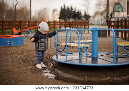 Little Boy Dressed In A Warm Hat And Jacket Playing Near The Carousel On The Playground