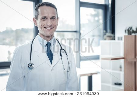 Prepare For Work. Qualified Confident Handsome Doctor Standing In The Cabinet Feeling Good Himself A