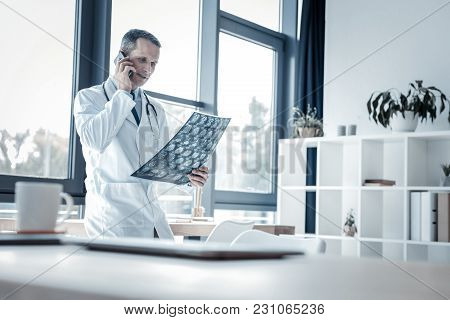 I Need More Information. Serious Calm Busy Doctor Standing In The Room Near The Window Holding X-ray