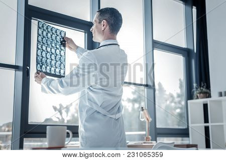 Lets Look. Interested Concentrated Skilled Professional Standing Near The Window Overlooking X-ray S
