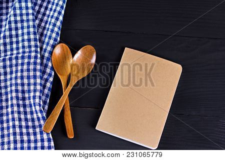 Blue Kitchen Towel In A Box And A Book For Recording Recipes On Dark Boards.