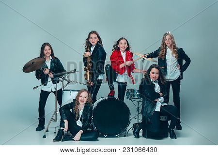 Teen Music Band Performing In A Recording Studio. The Group Of Girls Standing Together And Posing At