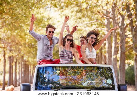 Friends stand waving from the back of an open top car