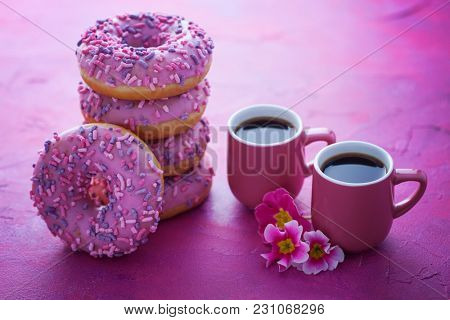 delicious pink donuts on pink background - sweet food