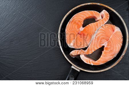 Close-up Of Raw Pink Salmon Steaks In A Frying Pan, Top View