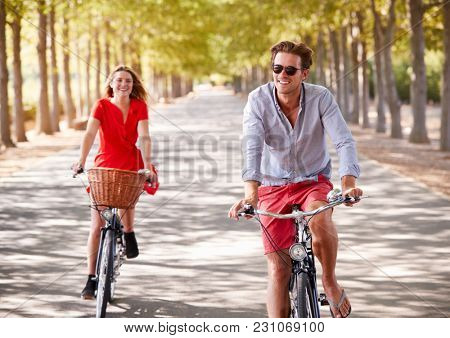 Young white adult couple riding bikes on a tree lined road