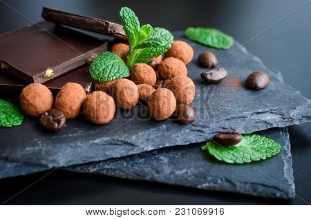 Heap Of Dark Chocolate Bars And Coffee Beans Candy Covered With Chocolate With Green Mint Leaves On
