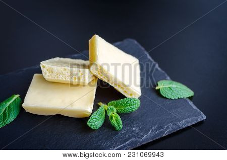 Heap Of Aerated Porous White Chocolate Bars With Green Mint Leaves On Dark Slate Board On Black Back