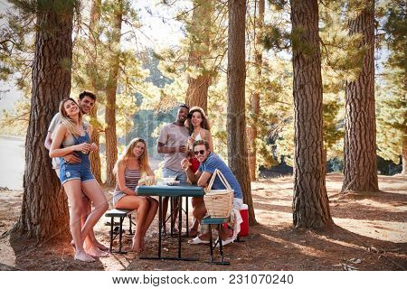 Group of adult friends by a lake smiling to camera