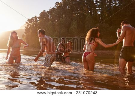 Young adult friends on vacation playing in a lake