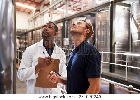 Two men inspecting vats in a modern winemaking factory