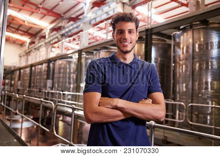 Portrait of a young Hispanic man working at a wine factory
