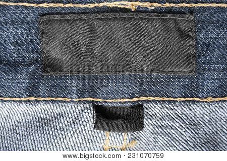 Blank Black Textile Clothes Label On Blue Denim Background Closeup