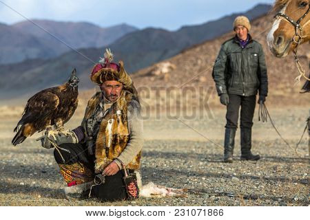SAGSAY, MONGOLIA - SEP 28, 2017: Berkutchi (Eagle Hunter) while hunting to the hare with a golden eagles on his arms in the mountains of Bayan-Olgii aimag.