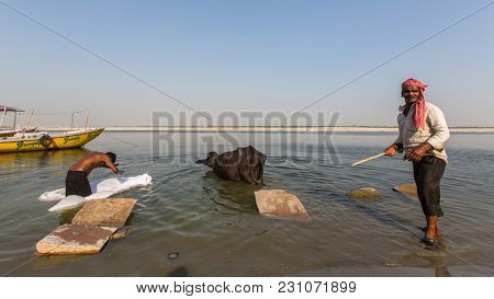 VARANASI, INDIA - MAR 13, 2018: A man washes sheets in the Holy Ganga river. Varanasi is one of the most important pilgrimage sites in India and is one of the 7 sacred cities of Hinduism.